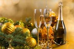 Champán festivo y regalos con las decoraciones del oro Fotografía de archivo