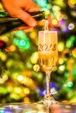 Champán o wine 2018 vidrios en fondo chispeante Imagen de archivo