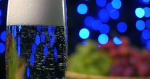 Champán que burbujea que es vertido en dos cristales contra backgroung del negro del boke almacen de video