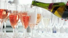 Champán que vierte en vidrios, mano de la mujer que sostiene la botella y que vierte el champán color de rosa en vidrios almacen de metraje de vídeo