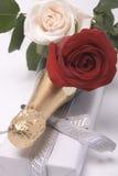 Champán, regalo y rosas Fotografía de archivo libre de regalías