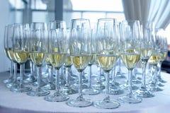 Champán semilleno o vidrios burbujeantes exhibidos en una tabla cubierta en el mantel blanco Foto de archivo