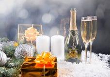 Champán, velas y regalos en aún vida festiva Imagen de archivo