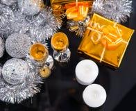 Champán y velas festivos con los regalos de oro Fotos de archivo