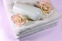 Champú, color de rosa y toallas Imágenes de archivo libres de regalías