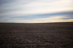 Champ agricole au loin labouré vide au coucher du soleil Photo libre de droits