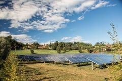 Champ central de l'électricité de panneau solaire dans le jour ensoleillé avec le ciel bleu et les nuages Images stock