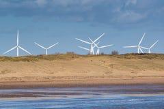 Champ d'éoliennes au delà des dunes de sable Image stock
