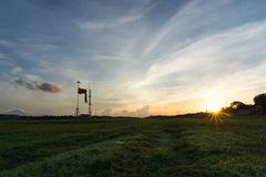 Champ d'herbe avec le lever de soleil et le fond de ciel bleu image stock