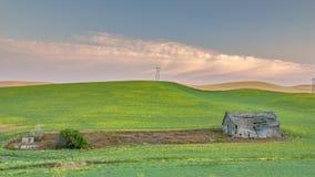 Champ de ferme labouré autour d'une grange au lever de soleil Photos stock