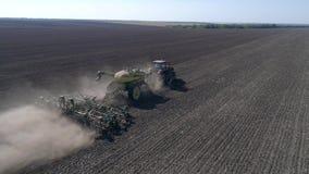 Champ de grain d'encemencement, tracteur avec le semoir et grain de graine de charrue dans le sol à planter la saison à l'automne banque de vidéos
