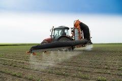 Champ de pulvérisation de haricot de soja de tracteur le protégeant contre des parasites photographie stock libre de droits