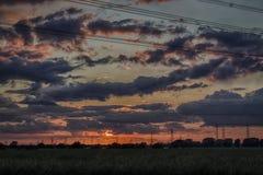 Champ des pylônes de l'électricité au coucher du soleil Image libre de droits
