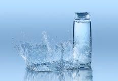 Champô hidratando no fundo da água azul com respingo grande em torno da garrafa Imagem de Stock