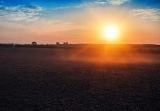 Champ labouré et beau coucher du soleil Images stock