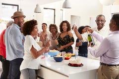 Champ?n de apertura envejecido medio del hombre afroamericano a celebrar en casa con su familia de tres generaciones fotografía de archivo
