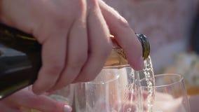Champagne ? versata in parecchi vetri Primo piano delle bottiglie e dei vetri archivi video