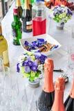 CHAMPAGNE, κρασί, λουλούδια, μπουφές καραμελών, γάμος υπαίθρια Στοκ Φωτογραφίες