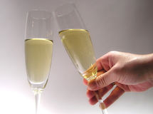 Champagne. One hand clinking a glass of champagne with another. (New Year's Eve Royalty Free Stock Images