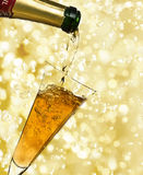 Champagne. Pouring champagne and holiday lights Royalty Free Stock Photo
