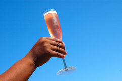 Champagne. An African American black female hand holding a champagne glass with red sparkling wine in front of blue sky background Royalty Free Stock Photos