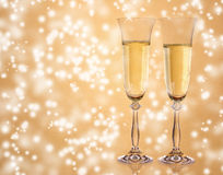Champagne. Pair of champagne glasses on golden sparkle blur background Stock Photos