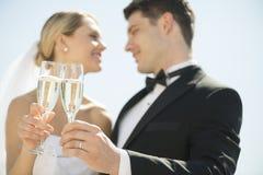 Νύφη και νεόνυμφος που ψήνουν τα φλάουτα CHAMPAGNE ενάντια στον ουρανό Στοκ Εικόνες