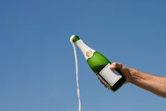 Champagne. Hand holding an open bottle of champagne on a background of the blue sky Royalty Free Stock Images