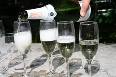 Champagne. Bottle of champagne is in a hand. The person pours champagne in glasses Stock Photo