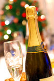 Champagne. Fluted glass and champagne bottle with Christmas tree on background Royalty Free Stock Images