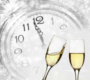 Champagne against holiday lights and clock close to midnight Stock Photos