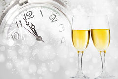 Champagne against holiday lights and clock close to midnight Royalty Free Stock Photography