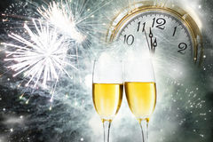 Champagne against holiday lights and clock close to midnight Stock Images