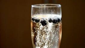 Champagne avec les myrtilles surgelées créant l'effet gentil de bulle après avoir ajouté plus de la bouteille clips vidéos