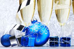 Champagne and balls. Glasses of champagne and decorative christmas balls on glitter background stock images