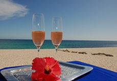 Champagne at the beach. Two glasses with pink champagne on a silver tray, beach in the back ground royalty free stock images