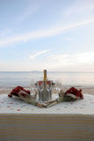 Champagne on the beach. Bottle of chilled champagne and wine glasses on a table at the beach - romantic setting stock photography