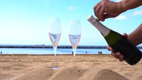 Champagne on beach. Someones hands opening bottle and pouring drink into the glasses stock video