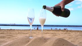 Champagne on beach. Someones hands pouring drink into the glasses, slow motion stock video