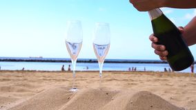 Champagne on beach. Someones hands opening bottle of champagne and pouring drink into the glasses stock video footage