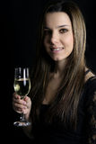 Champagne - beautiful woman holding a champagne flute. Beautiful woman holding a xhampagne flute over a black background royalty free stock images