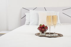 Champagne in bed. In a hotel room, ice bucket, glasses and fruits on white linen Stock Photo