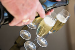 Champagne being poured. Into flutes on a glass table Royalty Free Stock Photos