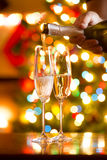 Champagne being poured in glasses against Christmas lights Royalty Free Stock Image