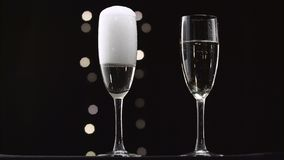 Champagne being poured into two transparent glass. Bokeh blinking black background. Champagne being poured into two transparent glass it sparkles and foams stock video