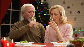 Champagne bevente anziano della moglie e del marito la vigilia di natale, luci dell'albero che scintillano stock footage