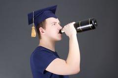 Champagne bevente del giovane uomo di graduazione sopra grey Immagine Stock Libera da Diritti