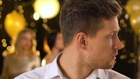 Champagne bevente del maschio infelice geloso al partito da solo, mentre altri che si divertono archivi video