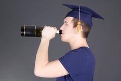 Champagne bevente dell'uomo di graduazione sopra grey Fotografie Stock Libere da Diritti