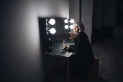 Champagne bevente della donna bionda premurosa vicino allo specchio nello spogliatoio Immagini Stock Libere da Diritti
